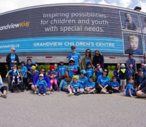 Grandview kids posing in front of a truck with a Grandview banner spread across it