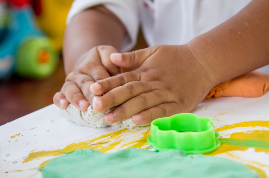 Image of a little child kneading play-dough.