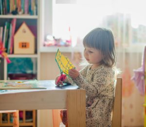 Toddler girl cutting paper with small pink scissors.