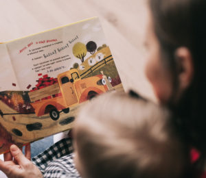 Woman reading book to toddler.