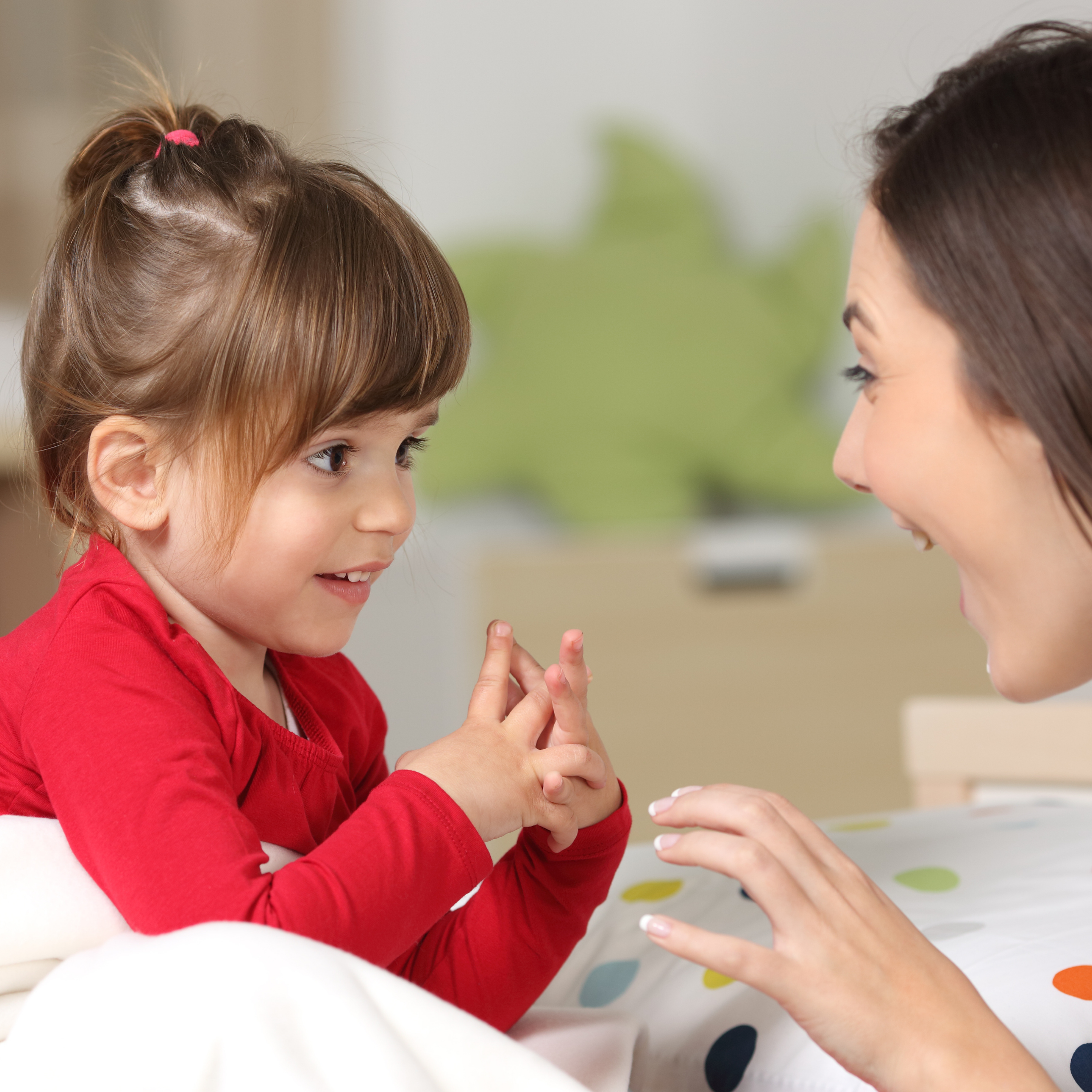 Little girl talking with mother in bed