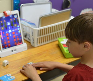 Little boy playing a game on an iPad