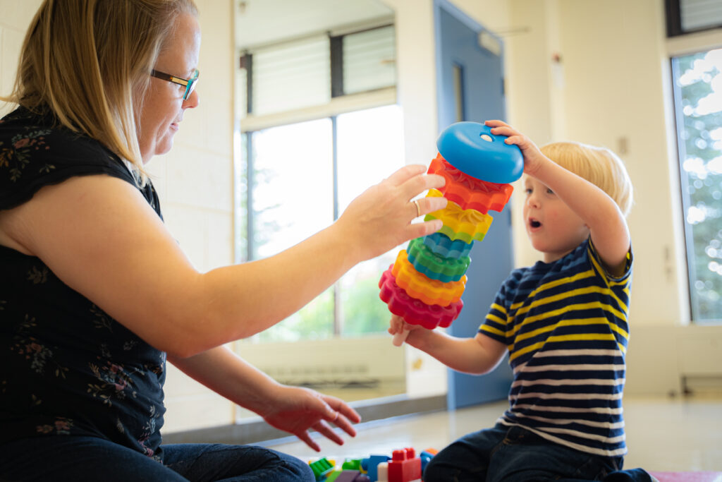 Little boy and his mom in a Grandview Kids Therapy Room playing with a rainbow-coloured toy.