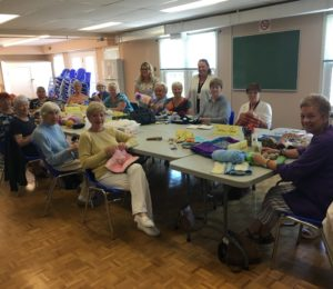 Crafters at their stations creating fidget muffs for Grandview Kids