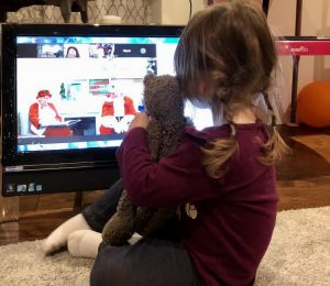 Little girl holding her stuffed animal close to her, sits in front of her computer on Zoom with Santa and Mrs. Claus.