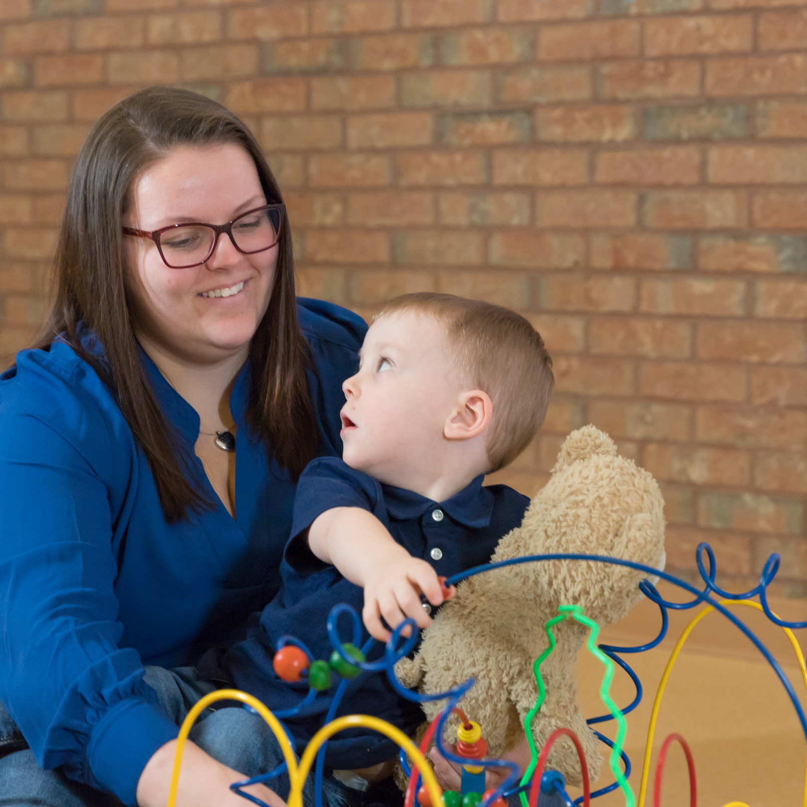 Mother holding son in her lap as he plays with the toys in front of them.