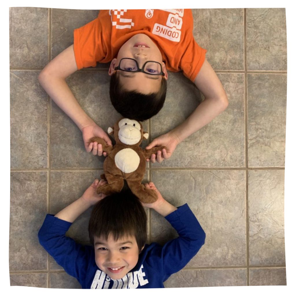 Two boys on the floor practicing the head-to-head rolling technique.