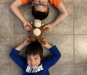Children laying on the floor holding a monkey toy together.