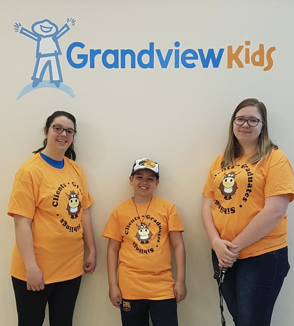 YAC Committee posing in front of the Grandview Kids logo
