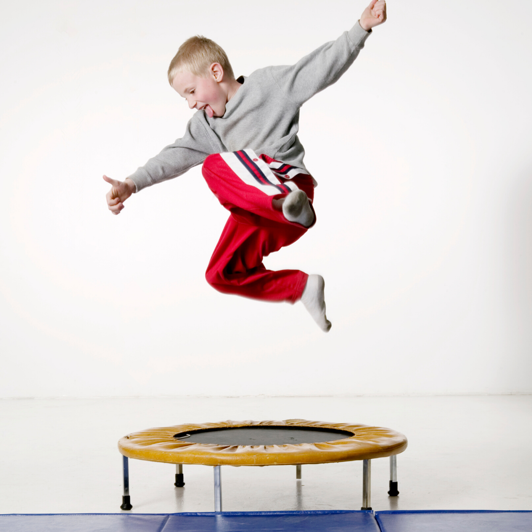 Boy mid-air after jumping on a trampoline.
