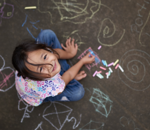 Little girl looking up at the camera while playing with sidewalk chalk on the pavement.
