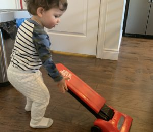 Toddler boy playing with a toy vacuum.