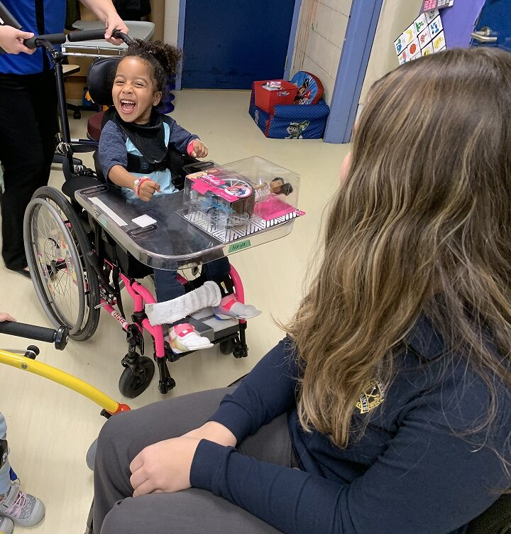 Little girl in wheelchair excited about her new barbie toy
