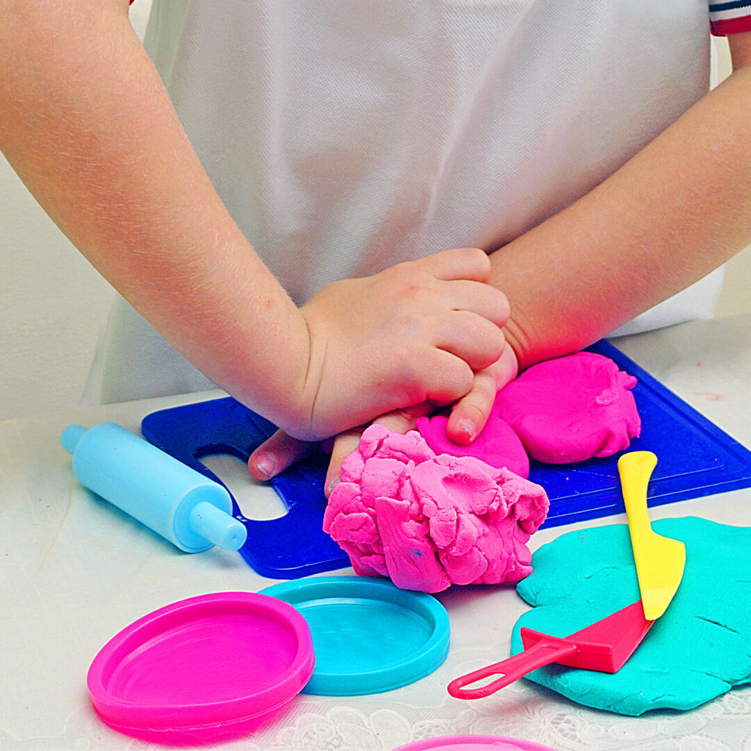 Child playing with playdough on a small blue cutting board.