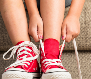 Small child tying shoelaces.