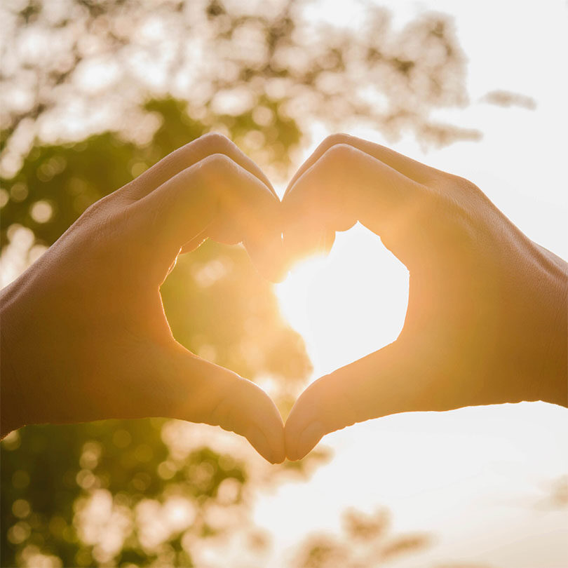 Person making a heart with their hands over the sun